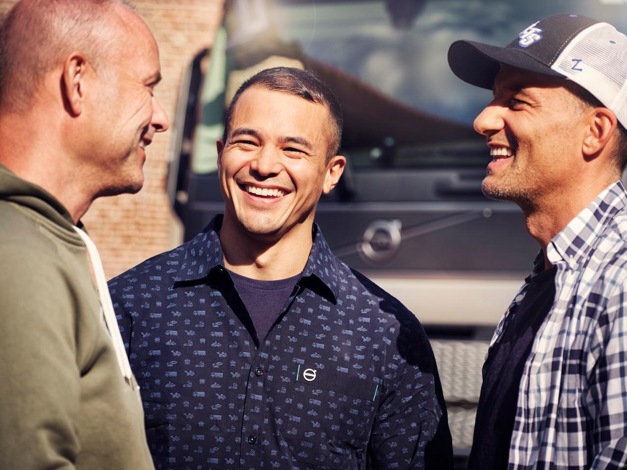 Nahaufnahme von drei Männern, die lächelnd vor einem Volvo-Lkw stehen